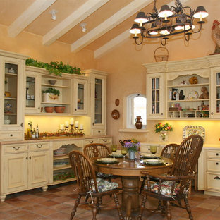 Inspiration for a large traditional u-shaped kitchen in Santa Barbara with raised-panel cabinets, light wood cabinets, limestone benchtops and terra-cotta floors.