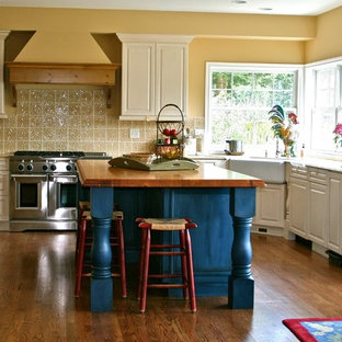Design ideas for a transitional u-shaped separate kitchen in Seattle with a farmhouse sink, wood benchtops, raised-panel cabinets, yellow splashback, stainless steel appliances, white cabinets, ceramic splashback and medium hardwood floors.
