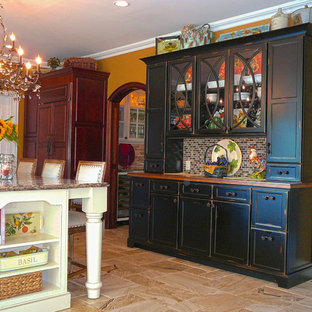 Photo of a large midcentury galley eat-in kitchen in New York with a farmhouse sink, raised-panel cabinets, distressed cabinets, panelled appliances, with island, granite benchtops, glass tile splashback and porcelain floors.