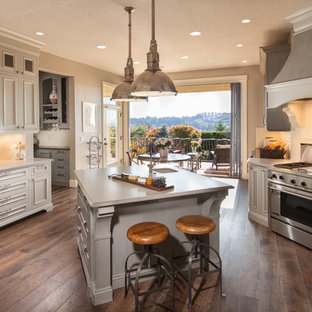 Large transitional enclosed kitchen inspiration - Inspiration for a large transitional u-shaped medium tone wood floor and brown floor enclosed kitchen remodel in Portland with stainless steel appliances, an island, an undermount sink, beaded inset cabinets, white cabinets, quartzite countertops, white backsplash and subway tile backsplash