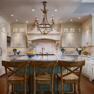 Large french country enclosed kitchen ideas - Large french country u-shaped dark wood floor enclosed kitchen photo in Chicago with a farmhouse sink, raised-panel cabinets, beige cabinets, white backsplash, paneled appliances, an island, quartz countertops and glass tile backsplash