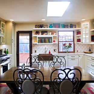 Example of an eclectic u-shaped eat-in kitchen design in Austin with a farmhouse sink, recessed-panel cabinets, white cabinets, white backsplash and stainless steel appliances