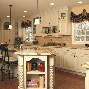 Esempio di una grande cucina chic con lavello sottopiano, ante con bugna sagomata, ante bianche, top in granito, paraspruzzi beige, elettrodomestici in acciaio inossidabile, pavimento in legno massello medio e isola