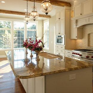 Zweizeilige, Große Klassische Wohnküche mit Triple-Waschtisch, profilierten Schrankfronten, weißen Schränken, Granit-Arbeitsplatte, Küchenrückwand in Weiß, Rückwand aus Backstein, Küchengeräten aus Edelstahl, gebeiztem Holzboden und Kücheninsel in Sonstige