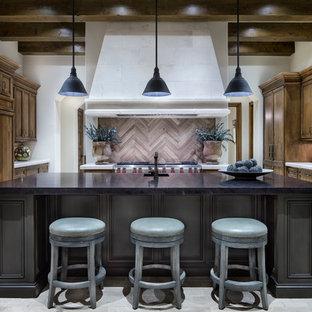 Esempio di una cucina mediterranea con ante con riquadro incassato, ante in legno bruno, paraspruzzi multicolore, elettrodomestici in acciaio inossidabile e isola