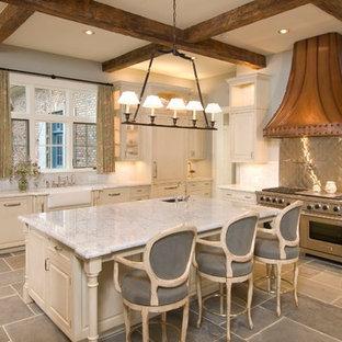 Idee per una cucina a L con lavello stile country, ante con bugna sagomata, ante beige, paraspruzzi a effetto metallico, elettrodomestici in acciaio inossidabile e isola
