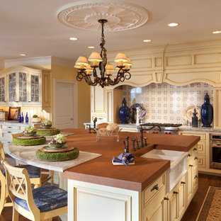Traditional eat-in kitchen designs - Example of a classic l-shaped dark wood floor eat-in kitchen design in Other with a farmhouse sink, raised-panel cabinets, yellow cabinets, wood countertops, multicolored backsplash, stainless steel appliances and an island