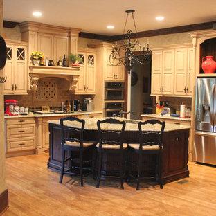 Geschlossene, Große Klassische Küche mit profilierten Schrankfronten, beigen Schränken, Rückwand aus Keramikfliesen, Küchengeräten aus Edelstahl, braunem Holzboden und Kücheninsel in Sonstige