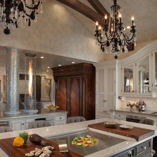 Geräumige Klassische Wohnküche mit Unterbauwaschbecken, Kassettenfronten, beigen Schränken, Küchenrückwand in Weiß, Rückwand aus Marmor, Kalkstein, zwei Kücheninseln, beigem Boden und grauer Arbeitsplatte in Sonstige