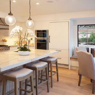 Exempel på ett litet beige beige kök, med en undermonterad diskho, luckor med upphöjd panel, vita skåp, bänkskiva i glas, vitt stänkskydd, stänkskydd i stenkakel, rostfria vitvaror, ljust trägolv, en köksö och beiget golv