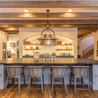 This is an example of a large mediterranean galley open plan kitchen in Houston with a farmhouse sink, beaded inset cabinets, blue cabinets, soapstone benchtops, white splashback, subway tile splashback, panelled appliances, dark hardwood floors and with island.
