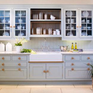 Diseño de cocina campestre con fregadero sobremueble, armarios con paneles empotrados, puertas de armario azules y salpicadero azul