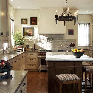 オレンジカウンティのおしゃれなコの字型キッチン (シルバーの調理設備、ベージュのキャビネット) の写真