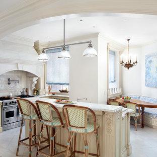 ニューヨークの中サイズのヴィクトリアン調のおしゃれなキッチン (アンダーカウンターシンク、落し込みパネル扉のキャビネット、ベージュのキャビネット、大理石カウンター、白いキッチンパネル、モザイクタイルのキッチンパネル、シルバーの調理設備の、ライムストーンの床) の写真