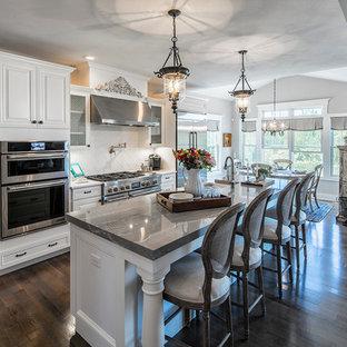 ニューヨークの中サイズのエクレクティックスタイルのおしゃれなキッチン (エプロンフロントシンク、落し込みパネル扉のキャビネット、白いキャビネット、クオーツストーンカウンター、白いキッチンパネル、セラミックタイルのキッチンパネル、シルバーの調理設備の、濃色無垢フローリング、茶色い床、グレーのキッチンカウンター) の写真