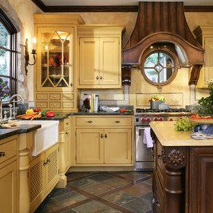 Bild på ett stort kök, med luckor med profilerade fronter, en rustik diskho, gula skåp, bänkskiva i täljsten, gult stänkskydd, rostfria vitvaror, skiffergolv, stänkskydd i mosaik, en köksö och brunt golv