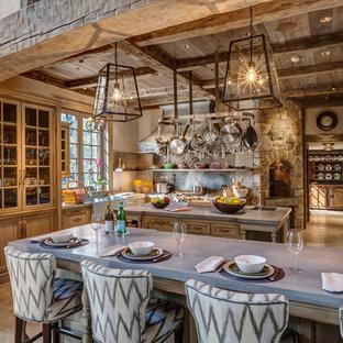 ニューヨークのトラディショナルスタイルのおしゃれなアイランドキッチン (ガラス扉のキャビネット、中間色木目調キャビネット、エプロンフロントシンク、コンクリートカウンター、ベージュキッチンパネル、セラミックタイルのキッチンパネル、シルバーの調理設備、ライムストーンの床) の写真