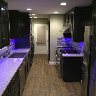 Mid-sized transitional galley separate kitchen in Orange County with a farmhouse sink, shaker cabinets, black cabinets, terrazzo benchtops, multi-coloured splashback, matchstick tile splashback, stainless steel appliances, porcelain floors, no island and brown floor.