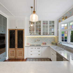 Photo of a transitional u-shaped kitchen in Melbourne with a farmhouse sink, louvered cabinets, white cabinets, multi-coloured splashback, mosaic tile splashback, stainless steel appliances, dark hardwood floors, a peninsula, brown floor and grey benchtop.