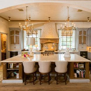 Пример оригинального дизайна: п-образная кухня-гостиная в средиземноморском стиле с одинарной раковиной, синими фасадами, желтым фартуком, техникой под мебельный фасад, фасадами с выступающей филенкой и столешницей из известняка