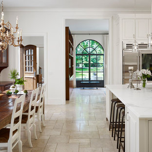 Design ideas for a traditional u-shaped eat-in kitchen in Chicago with a single-bowl sink, white cabinets, marble benchtops, white splashback, stone slab splashback, stainless steel appliances, travertine floors and with island.