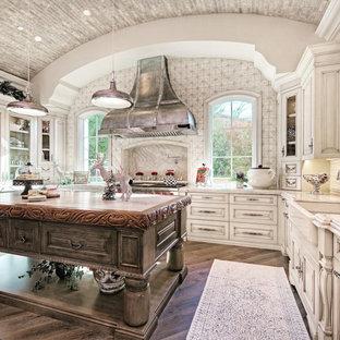 フェニックスの巨大なシャビーシック調のおしゃれなキッチン (エプロンフロントシンク、レイズドパネル扉のキャビネット、淡色木目調キャビネット、珪岩カウンター、マルチカラーのキッチンパネル、磁器タイルのキッチンパネル、シルバーの調理設備の、濃色無垢フローリング、茶色い床、ベージュのキッチンカウンター) の写真
