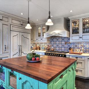 オレンジカウンティの中くらいの地中海スタイルのおしゃれなキッチン (アンダーカウンターシンク、落し込みパネル扉のキャビネット、白いキャビネット、木材カウンター、マルチカラーのキッチンパネル、パネルと同色の調理設備、モザイクタイルのキッチンパネル、濃色無垢フローリング、茶色い床) の写真