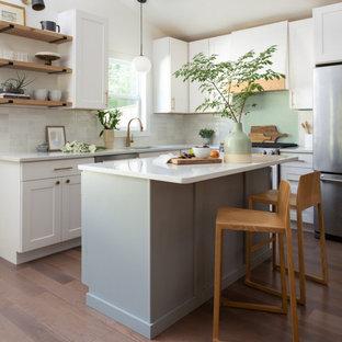 Idéer för vintage vitt l-kök, med en undermonterad diskho, skåp i shakerstil, vita skåp, vitt stänkskydd, rostfria vitvaror, mellanmörkt trägolv, en köksö och brunt golv
