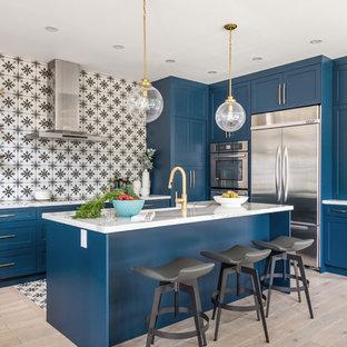Diseño de cocina clásica renovada con armarios estilo shaker, puertas de armario azules, salpicadero multicolor, electrodomésticos de acero inoxidable, suelo de madera clara, una isla, suelo beige y encimeras blancas