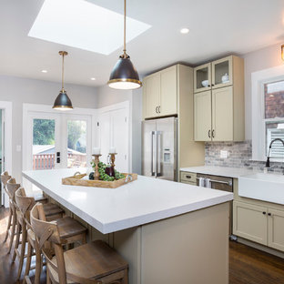 Mid-sized transitional eat-in kitchen designs - Eat-in kitchen - mid-sized transitional l-shaped dark wood floor and brown floor eat-in kitchen idea in San Francisco with a farmhouse sink, shaker cabinets, quartz countertops, gray backsplash, stone tile backsplash, stainless steel appliances, an island and beige cabinets
