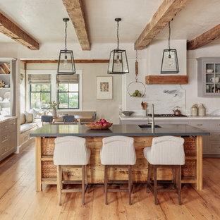ボストンのカントリー風おしゃれなキッチン (エプロンフロントシンク、シェーカースタイル扉のキャビネット、グレーのキャビネット、白いキッチンパネル、石スラブのキッチンパネル、パネルと同色の調理設備、無垢フローリング、茶色い床、白いキッチンカウンター) の写真