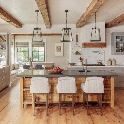 Cottage u-shaped medium tone wood floor and brown floor kitchen photo in Boston with a farmhouse sink, shaker cabinets, gray cabinets, white backsplash, stone slab backsplash, paneled appliances, an island and white countertops