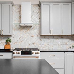 他の地域のカントリー風おしゃれなキッチン (アンダーカウンターシンク、シェーカースタイル扉のキャビネット、青いキャビネット、クオーツストーンカウンター、黄色いキッチンパネル、磁器タイルのキッチンパネル、白い調理設備、無垢フローリング、茶色い床、黒いキッチンカウンター、三角天井) の写真