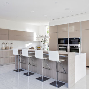 Design ideas for a small modern l-shaped open plan kitchen in Los Angeles with flat-panel cabinets, beige cabinets, quartz benchtops, white splashback, stainless steel appliances, porcelain floors and with island.