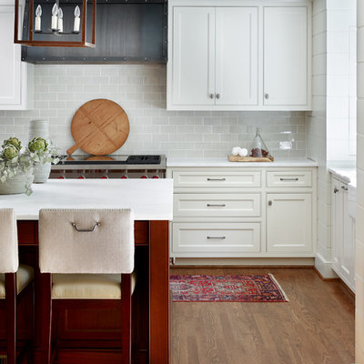 Mid-sized transitional u-shaped medium tone wood floor and brown floor enclosed kitchen photo in Atlanta with beaded inset cabinets, white cabinets, gray backsplash, an island, a farmhouse sink, subway tile backsplash, stainless steel appliances and marble countertops