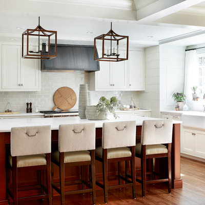 Mid-sized transitional u-shaped medium tone wood floor and brown floor kitchen photo in Atlanta with an island, a farmhouse sink, beaded inset cabinets, white cabinets, gray backsplash, subway tile backsplash, stainless steel appliances and marble countertops