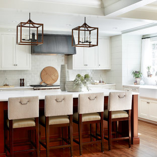 Mid-sized transitional enclosed kitchen remodeling - Mid-sized transitional u-shaped medium tone wood floor and brown floor enclosed kitchen photo in Atlanta with an island, a farmhouse sink, beaded inset cabinets, white cabinets, gray backsplash, subway tile backsplash, stainless steel appliances and marble countertops