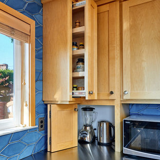 Mid-sized contemporary u-shaped eat-in kitchen in Other with an integrated sink, shaker cabinets, light wood cabinets, stainless steel benchtops, blue splashback, ceramic splashback, stainless steel appliances, linoleum floors, a peninsula and brown floor.