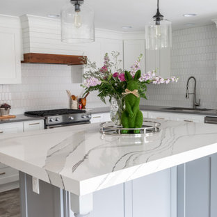This is an example of a mid-sized country l-shaped eat-in kitchen in Atlanta with an undermount sink, shaker cabinets, white cabinets, quartz benchtops, white splashback, ceramic splashback, stainless steel appliances, vinyl floors, with island, grey floor and white benchtop.