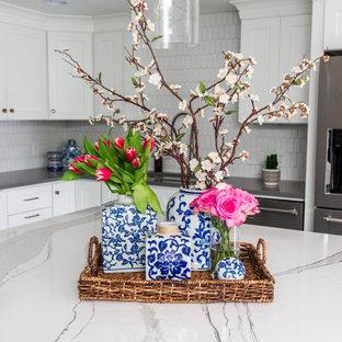 Bild på ett mellanstort lantligt vit vitt kök, med en undermonterad diskho, skåp i shakerstil, vita skåp, bänkskiva i kvarts, vitt stänkskydd, stänkskydd i keramik, rostfria vitvaror, vinylgolv, en köksö och grått golv
