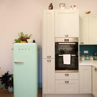 Esempio di una cucina minimal di medie dimensioni con lavello a doppia vasca, ante in stile shaker, ante verdi, top in superficie solida, paraspruzzi bianco, elettrodomestici da incasso, parquet chiaro e nessuna isola