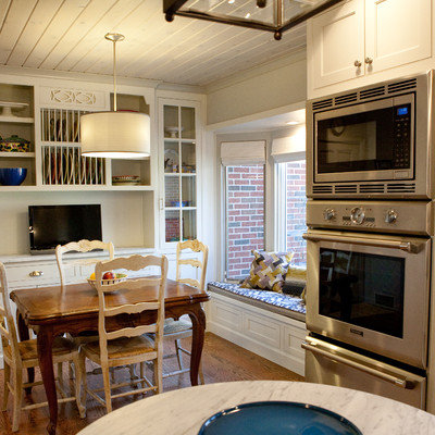 Elegant galley eat-in kitchen photo in Other with glass-front cabinets, white cabinets, white backsplash, stone tile backsplash and stainless steel appliances