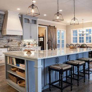 Idéer för ett klassiskt kök och matrum, med en rustik diskho, skåp i shakerstil, grå skåp, grått stänkskydd, stänkskydd i stenkakel, rostfria vitvaror, mörkt trägolv, en köksö och brunt golv