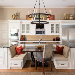 Photo of a large traditional kitchen/diner in Dallas with white cabinets, beige splashback, stainless steel appliances, light hardwood flooring and an island.