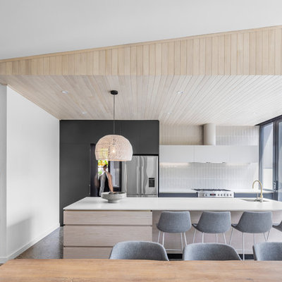 Inspiration for a contemporary galley concrete floor and gray floor eat-in kitchen remodel in Adelaide with an undermount sink, flat-panel cabinets, light wood cabinets, white backsplash, stainless steel appliances, an island and white countertops