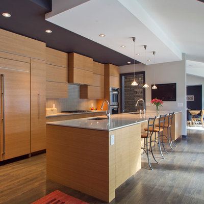 Example of a mid-sized minimalist galley medium tone wood floor and brown floor eat-in kitchen design in Atlanta with flat-panel cabinets, medium tone wood cabinets, gray backsplash, paneled appliances, a single-bowl sink, ceramic backsplash, a peninsula and quartzite countertops