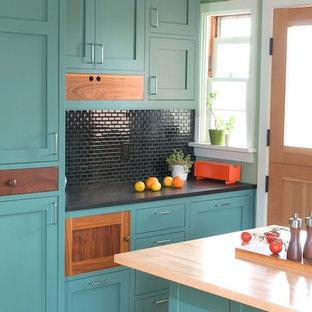 Idée de décoration pour une cuisine design avec des portes de placard turquoises, un placard à porte shaker, une crédence noire et une crédence en mosaïque.
