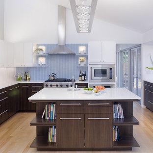 Exempel på ett modernt u-kök, med rostfria vitvaror, en undermonterad diskho, släta luckor, skåp i mörkt trä och blått stänkskydd