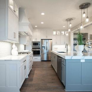 Стильный дизайн: угловая кухня-гостиная в стиле кантри с накладной раковиной, белыми фасадами, белым фартуком, техникой из нержавеющей стали, паркетным полом среднего тона, островом, коричневым полом и белой столешницей - последний тренд