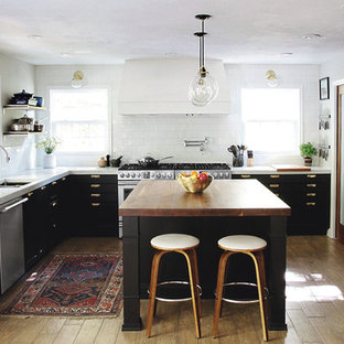 Transitional kitchen appliance - Example of a transitional kitchen design in Charlotte with a double-bowl sink, black cabinets, wood countertops, white backsplash, subway tile backsplash, stainless steel appliances and an island